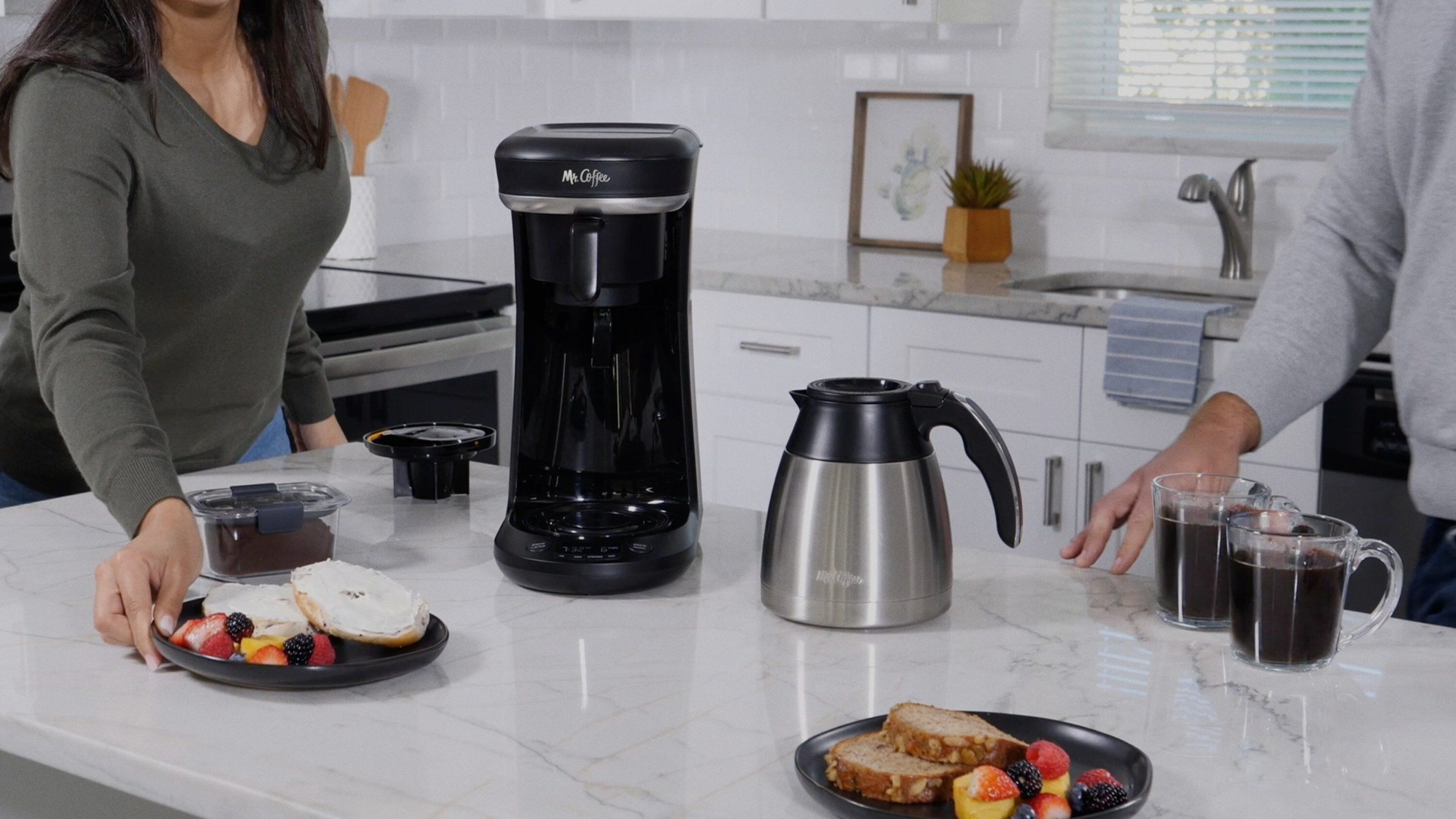 coffee maker with thermal carafe in kitchen with people and breakfast foods